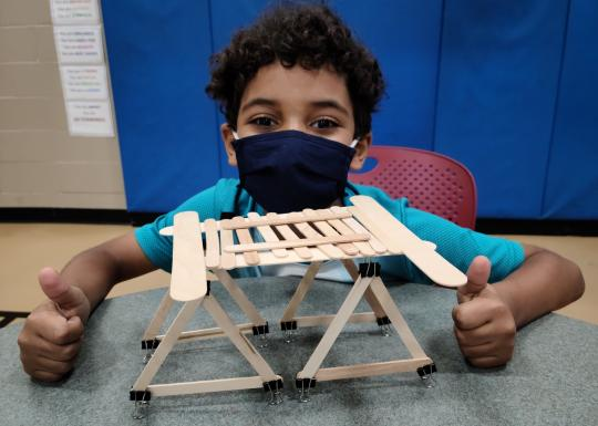 Young boy making a popsicle stick model