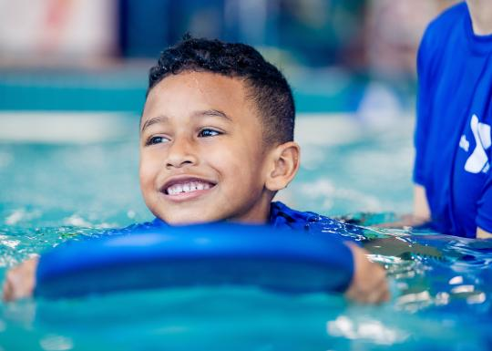 YMCA Youth Swim Lessons - Child On Paddle Board