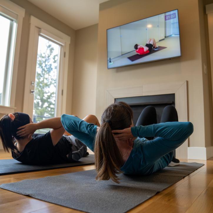 Mother and daughter doing sit ups together at home