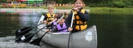 Four children canoeing at Camp Lake Helena